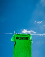 Volunteer t-shirt hanging on a clothesline against a blue sky.