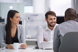 Three happy coworkers sitting down to have a meeting