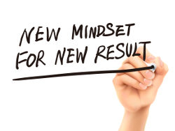 new mindset for new results words written by hand on a transparent board