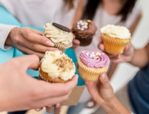 Group of friends eating cupcakes