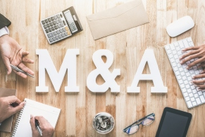 Top view of business office workstation with M&A letters or merger and acquisition