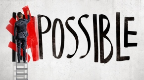 A businessman stands on a stepladder and hides the word Impossible written on the wall using a red paint roller.