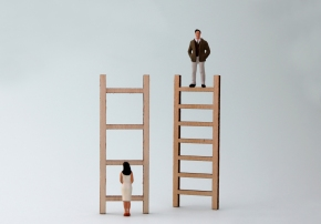 Wooden ladders and miniature people. The concept of gender inequality in promotion.