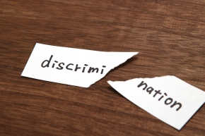 The paper written as discrimination is torn on wood. Concept of abolition of discrimination.