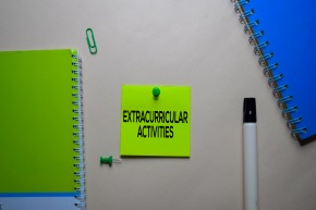 Extracurricular Activities text on sticky notes at office desk.