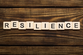 Resilience written out with scrabble pieces on wooden table